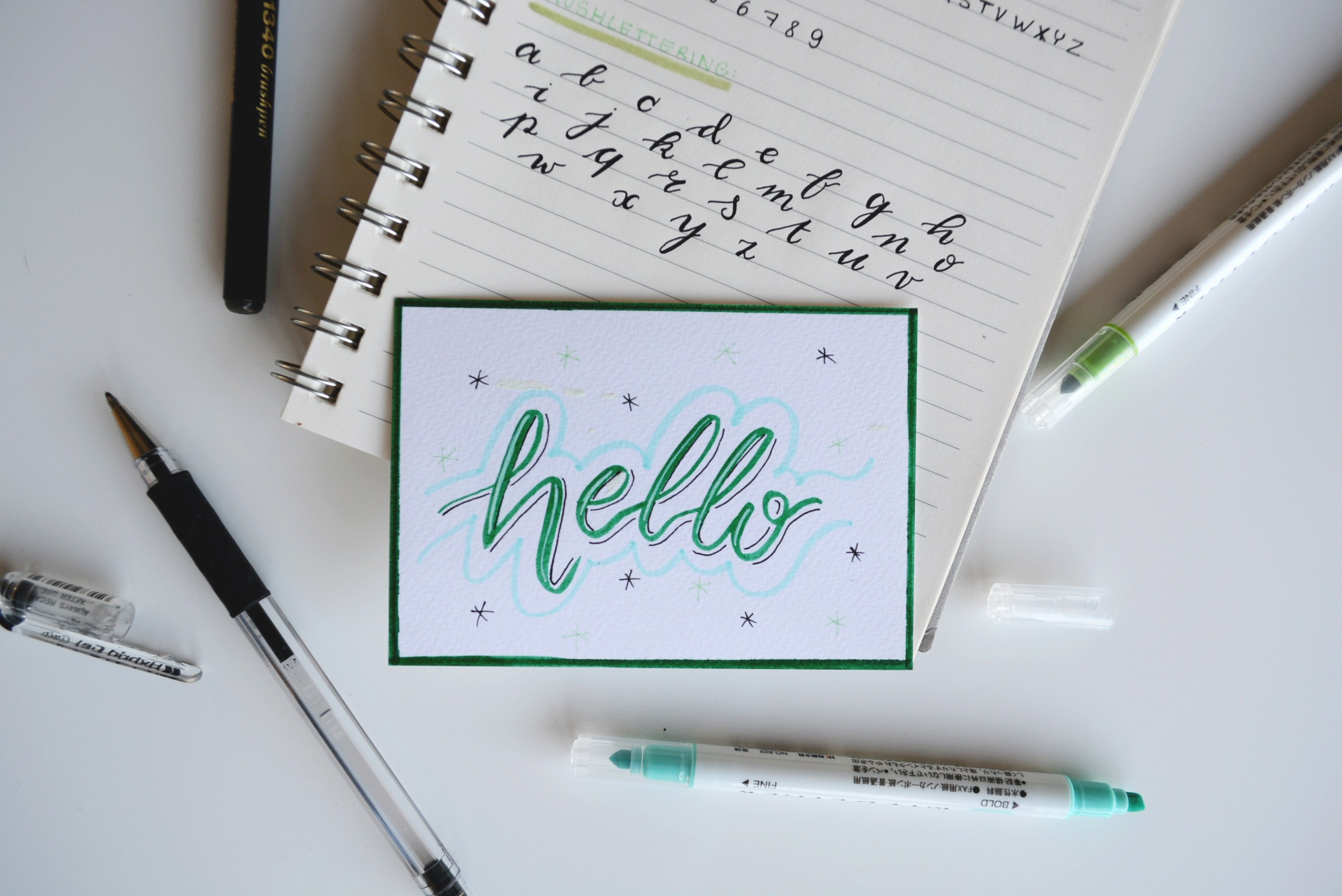 pens and markers along with notepads and a card saying hello
